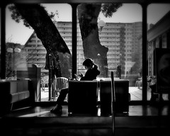 Sunny Spot... (明遊快) Tags: monochrome bw city urban architecture building window trees sunlight woman winter table sitting shadows lines sunny dusk evening japan candid happyplanet asiafavorites