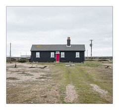 Weatherboarded Beach Home, Dungeness, Kent, England. (Joseph O'Malley64) Tags: weatherboardedbeachhome weatherboarding dungenessbeach dungeness kent england uk britain british greatbritain thebuiltenvironment newtopography newtopographics manmadestructure manmadeenvironment housing home dwelling abode beachhome bungalow woodencladding brickwork bricksmortar cement pointing chimneystack chimney chimneypots corrugatedsteelroofingpanels zinkflashing doubleglazing upvcdoubleglazing windows doorway door woodendoor doorstep bench pylons electricitypylons powerlines nationalgrid nationalgridpowerlines woodenpoles gorse gorsebushes gravel shingle dustbin buoys grass desolate expanse landscape ornamentalstonework coast coastal seaside thebritishseaside fujix fujix100t accuracyprecision architecture architecturalphotography documentaryphotography britishdocumentaryphotography
