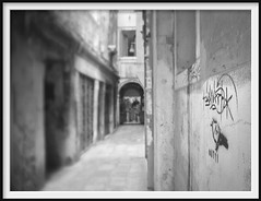 waiting (the-photon-trap) Tags: waiting venice venezia italy italia alley streetart graffiti monochrome bw blackandwhite ir infrared microfourthirds m43 olympusomdem5mk2 thephotontrap tiltshift dof bokeh blur homemadelens