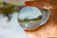 Street Through A Lensball. (dccradio) Tags: lumberton nc northcarolina robesoncounty outdoor outdoors outside independencedrive sky clouds nikon d40 dslr street paved pavement road tree trees foliage grass lawn greenery ground lightpole streetlight lamppost tensphy lensball glassball glassballphotography lensballphotography crystalball glass round circle