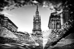 Time to reflect. (Mister G.C.) Tags: blackandwhite bw sonya6000 sonyalpha6000 mirrorless streetphotography urbanphotography candid street monochrome photograph image people urban town city architecture puddle water reflection building tower clock landmark stgeorgestronchurch nelsonmandelaplace sony a6000 35mmf18 sel35f18 35mm primelens schwarzweiss strassenfotografie glasgow scotland europe