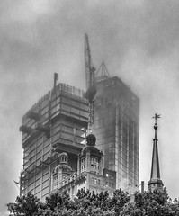 The New Rising Above the Old (allentimothy1947) Tags: groundzero manhattan newyorkstate worldtradecenter architecture buildings cloudy fog lowclouds memorial newyorkcity people rain reflections streets subway transportationbuildings