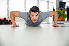 Handsome man doing push-ups in gym (wcn247) Tags: push ups man pushups gym sport training fit fitness workout trainer personal pressure leisure floor attractive activity sporty horizontal adult strong male people muscles concentrated healthy bodybuilder strength body doing person muscular athletic work health exercise musculine wear sportswear sportive happy