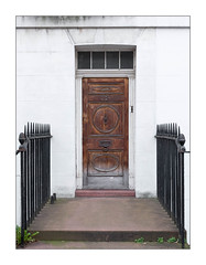 The Built Environment, North London England. (Joseph O'Malley64) Tags: thebuiltenvironment newtopography newtopographics manmadeenvironment manmadestructure building structure victorian victorianbuilding architecture architecturalfeatures architecturalphotography urbanlandscape britishdocumentaryphotography documentaryphotography townhouse house home northlondon london england uk britain british greatbritain doorway door woodenpanelleddoor entrance exit woodwork carvings faded damp patina doorknockers windows doorbell doorstep bootscraper railings ironwork ornamentalironwork blockwork stoneblockwork render dandelion weeds urban eastlondon eastend