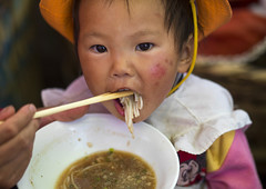 Chinese Baby Eating Noodles, Lijiang, Yunnan Province, China (Eric Lafforgue) Tags: 011months 23years a0007611 asia baby babyhood china chineseculture colorpicture day eastasianethnicity eating food foodanddrink frontview horizontal innocence lookingatcamera noodle portrait realpeople togetherness twopeople twopersons yunnan yunnanprovince lijiang