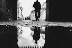 Am Boden (Zesk MF) Tags: bw black white street candid mirroring reflection spiegelung puddle rain dark man focus outoffocus cologne zesk x100f fuji