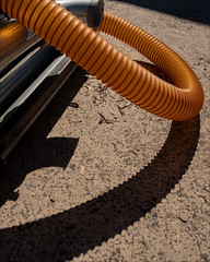 rowville-2082-ps-w (pw-pix) Tags: hose tube corrugated translucent brown orange yellow pipes bends aluminium plastic apparatus strange unknown weird shadow curved concrete leaves equipment neutronplace rowville easternsuburbs outereast melbourne victoria australia peterwilliams pwpix wwwpwpixstudio pwpixstudio