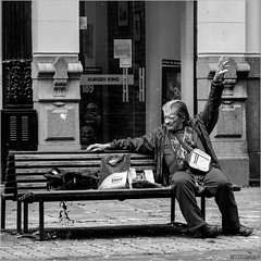 Burger King (John Riper) Tags: johnriper street photography straatfotografie square vierkant bw black white zwartwit mono monochrome john riper fuji fujifilm xt2 xf 18135 montevideo uruguay bench man burger king homeless tramp happy arm hand fingers