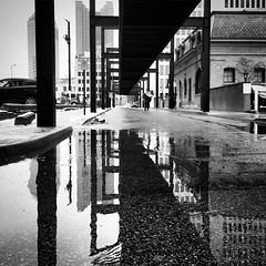 Capital Street (tim.perdue) Tags: iphne iphoneography apple se iphonese mobile capital street downtown columbus ohio urban city reflection puddle bridge skywalk road alley building black white bw monochrome blackandwhite