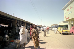 76-372 (ndpa / s. lundeen, archivist) Tags: nick dewolf color photograph 1976 1970s film 35mm 76 reel76 early1976 africa northernafrica northeastafrica sudan thesudan african sudanese khartoum town city citylife streetlife candid streetphotography people localpeople market streetmarket street sign signs building buildings car cars vehicle vehicles automobile automobiles bata bridge overpass men women tob tobs hijab hijabs headcovering headcoverings westernclothing tourist visitor schenck garretschenck hat shoppers shopping robes whiterobes turban jalabiya powerlines bluesky souq souk tobe khartoumstate photographbynickdewolf