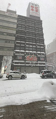 Snow Crab (sjrankin) Tags: 11january2019 edited sapporo hokkaido japan snow clouds winter roa cars buildings skyline city panorama advertisement restaurant crab
