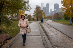 Rain Starting to Come Down Again (Jocey K) Tags: sonydscrx100m6 triptocanada ontario canada autumn trees walkway leaves wet clouds sky autumncolours pavement people architecture buildings bin