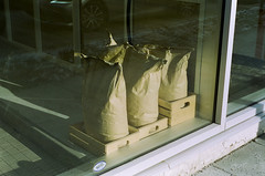 sacks of flour (gguillaumee) Tags: film analog cinestill colorfilm bags bakery saturation mtl montreal streetphotography leicam7 leica 50mm 35mm naturemorte rangerfinder