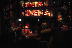 central cinema (markfly1) Tags: central cinema soho london city red orange yellow green low key full colour image street shot candid photograph man women girl mobile phone camera people sitting glow neon signs christmas trees presents ribbons windiw night gifts decorations lights lighting display ticket booth nikon d750 nikkor 50mm lens