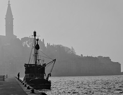 an interested tourist (heinzkren) Tags: schwarzweis blackandwhite bw sw monochrome panasonic lumix silhouette human ship tower church sea hr kai street streetphotography fog nebel quay wharf rovinj istrien fishingboat croatia innamoramento mood idyll