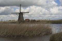 A windmill in Kinderdijk (2) (Roland B43) Tags: kinderdijk windmill clouds canal water reed takumarsmc50mm14