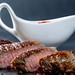 Juicy steak medium-rare slices with white gravy boat on a dark background