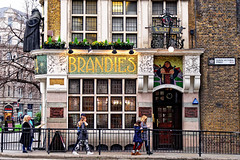 Brandies (Geoff Henson) Tags: pub publichouse brandy sculpture statue mosaic flowers lights pedestrians people railing barrier sign streetsign pavement sidewalk door window building architecture wall street road blackfriars cityoflondon