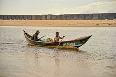 Day Done (Rod Waddington) Tags: africa afrique afrika madagascar malagasy fishermen water pirogue canoe boat oars rowing paddling breakwater beach sand father son subsistence fishing candid outdoor
