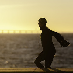 Runner at Västra Hamnen (Mabry Campbell) Tags: europe malmö scandinavia skane skåne sweden coast coastal image malmo person photo photograph photography running silhouette squarecrop sunset sverige västrahamnen woman yellow f35 mabrycampbell february 2012 february262012 201202262719 200mm ¹⁄₈₀₀sec 100 ef200mmf28liiusm