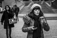 Juggling (Leanne Boulton) Tags: urban street candid portrait portraiture streetphotography candidstreetphotography candidportrait streetportrait streetlife woman female girl face expression mood feeling fringe beanie coffee smartphone modernliving juggling tone texture detail depthoffield bokeh naturallight outdoor light shade city scene human life living humanity society culture lifestyle people canon canon5dmkiii 70mm ef2470mmf28liiusm black white blackwhite bw mono blackandwhite monochrome glasgow scotland uk