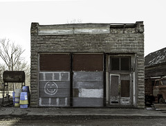 Smile! (unknown quantity) Tags: abandonedbusiness sky shadows corrugatedmetal rust graffiti boardedupwindows barewood crumblingsidewalk peelingpaint rot deterioration neglect junk weathered