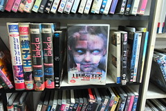 """Korea Suwon downtown near Seoul functioning video shop circa 2018 with """"Dawn of the Dead"""" remake for rent - """"Mall Walkers"""" (moreska) Tags: korea suwon vhs rental shop 2018 oldschool retro videocassette homeentertainment dawnofthedead 2004 icons classics zombie horror gore reboot spine clamshell misery 1991 genrefilms display graphics fonts hangul 1980s shops stores travel tourism rok asia"""