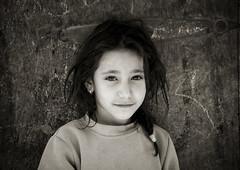 Portrait Of A Smiling Yemeni Girl, Sanaa, Yemen (Eric Lafforgue) Tags: arabia arabiafelix arabianpeninsula blackandwhite brighteye child cute darkhair day earrings girl horizontal innocence longhair oneperson placeofinterest portrait realpeople shy smile smiling street wall woman yemen yemeni younggirl youth img2256 sanaa