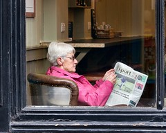 Sporting Life (sasastro) Tags: window cafe newspaper woman pink chair pentaxk5iis streetphotography candid burystedmunds uk