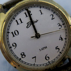 """No one?  """"Noon""""? (Coyoty) Tags: macromondays timepieces flickrfriday palindrome time watch timepiece clock noon noonenoon squareformat round circle numbers gold white blue square numerals sexatnoontaxes word wordplay humor funny tilt diagonal hands lines angle"""