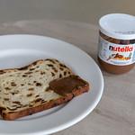 Früchtebrot, an einer Ecke mit Nutella bestrichen auf Teller neben Nutella-Glas thumbnail