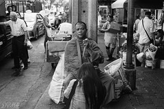 Almsgiving (D. R. Hill Photography) Tags: thailand thai bangkok asia southeastasia urban city blackandwhite monochrome grain film analog analogue 135 35mmfilm street streetphotography alms merit buddhist buddhism monk contax contaxg1 g1 carlzeissplanar45mmf2 zeiss 45mm primelens fixedfocallength kodak kodakfilm kodaktrix400 trix trix400