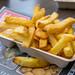 Pommes Frites mit Mayonnaise in Schale von Imbissbude steht auf Zeitung