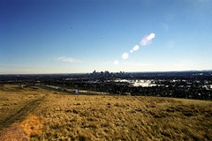 Nose Hill Park 1: Downtown Calgary (pmvarsa) Tags: winter 2002 analog film 135 cans2s kodak gold 200iso kodakgold200 nikonsupercoolscan9000ed nikon coolscan cold sky blue tan brown grass path trail landscape city skyline lens flare lensflare nose hill canon ftb canonftb classic camera calgary alberta canada ab