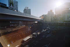Flare (OzGFK) Tags: 35mm fuji fujiindustrial100 japan nikonfm2n tokina1116mm tokyo analog bright city film pushedtwostops sunny travel sunflare lensflare ueno intersection traffic
