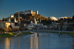 Salzburg and the snow of the Tennengebirge (echumachenco) Tags: city cityscape outdoor river water reflection light shadow mountainrange snow alps tennengebirge salzburg bridge müllnersteg fortress festung castle hohensalzburg cathedral dom evangelischechristuskirche kollegienkirche mönchsberg sky blue afternoon march austria österreich nikond3100