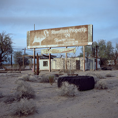 riverfront property $29 / route 66. essex, ca. 2016. (eyetwist) Tags: eyetwistkevinballuff eyetwist route66 billboard sign faded abandoned essex mojavedesert california mamiya 6mf 50mm kodak portra 160 mamiya6mf mamiya50mmf4l kodakportra160 ishootfilm analog analogue film emulsion mamiya6 square 6x6 120 filmexif epsonv750pro ishootkodak 6 mojave desert highdesert mediumformat motherroad us66 route 66 roadside america americana typology lonely desolate getyourkicksonroute66 kicks iconla signgeeks type typography americantypologies roadtrip weathered worn decay ruin wires roadsideamerica riverfront property 29 flamingo hilton casino laughlin nevada coloradoriver advertisement vintage old peeling tire