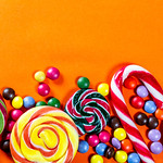 Colorful lollipops and candies on orange background thumbnail