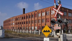 Early 20thC 'Industrial Functional' style: former Hewetson Shoe Factory, c1920, Brampton, Ontario. (edk7) Tags: nikond50 edk7 2006 canada ontario peelregion brampton 57millstreetnorth historic heritage designated hewetsonshoefactory architecture building oldstructure city cityscape urban redbrick early20thcindustrialfunctional sky chimney fence road track controlbox railwaylevelcrossinggate sign signage