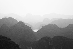 Layers of hills (Théo G-N) Tags: vietnam northern ha long bay travel trip landscape water paesaggio paysage noir blan black white nero bianco monochrome voyage viaggio mer ciel montagne ville brume cat ba layers hills mountains colline brouillard nebbia fog shades sfumature nuances