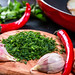 Sliced fresh parsley with garlic cloves and chili pepper on the kitchen Board