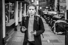 Two Way Communication (Leanne Boulton) Tags: portrait urban street candid portraiture streetphotography candidstreetphotography candidportrait streetportrait streetlife eyecontact candideyecontact woman female girl face eyes expression mood feeling pretty blonde mobile smartphone technology modernliving tone texture detail depthoffield bokeh naturallight outdoor light shade city scene human life living humanity society culture lifestyle people canon canon5dmkiii 70mm ef2470mmf28liiusm black white blackwhite bw mono blackandwhite monochrome hattongarden london england uk
