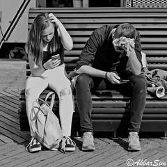 IT WAS A HOT DAY (Akbar Simonse) Tags: rotterdam rotjeknor roffa holland netherlands nederland streetphotography streetshot straatfotografie straatfoto people candid smartphone bench bank sitting hotday zwartwit bw blancoynegro bn monochrome vierkant square akbarsimonse urban man woman photographiederue straszenfotografie meisje