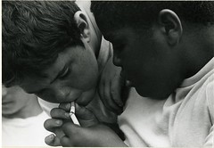 Two young boys lighting a cigarette from another cigarette (Cambridge Room at the Cambridge Public Library) Tags: cambridgemass cambridge massachusetts bw blackandwhite olivepierce pierceolive