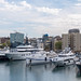 View from tourist attraction and bridge Rambla de Mar to yachts and luxury boats in Port Vell harbour with tower clock in Barcelona, Spain