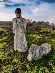The Good Shepherd (Steve Taylor (Photography)) Tags: shepherd crook donkey digitalart sculpture carving blue green brown stone rock man newzealand nz southisland canterbury christchurch grass bush texture sky cloud southnewbrighton sculpturepark