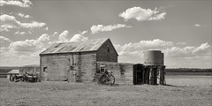hillside-2645-ps-w (pw-pix) Tags: rustic cliched old dilapidated weathered decayed broken disused barn shed dray wagon buggy doors windows tanks tankstand wood wooden iron corrugatediron steel galvanised rusted rusty corroded patina grey grass valley riverflats sky clouds bw blackandwhite monochrome toned bairnsdaledargoroad lindenowroad hillside eastgippsland gippsland victoria australia peterwilliams pwpix wwwpwpixstudio pwpixstudio
