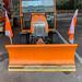 Oranges Fahrzeug von Iseki für Schneeräumung im Winter mit in Front montierter Schaufel und Flaggen