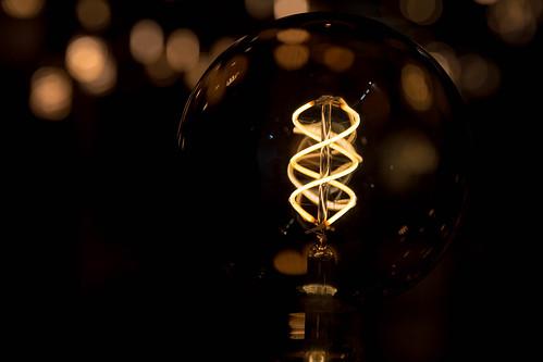 Glühbirne künstlerisch fotografiert im Dunkeln mit lediglich erhelltem Leuchtdraht