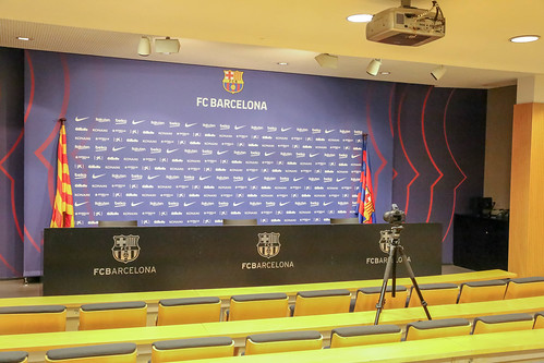 Press room with yellow seats for journalists and small stage for FC Barcelona players and staff members at Camp Nou in Catalonia, Spain